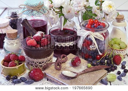 Recipe book with spoon of sugar and jars of berry and homemade jam. Making fruit jam concept. Fresh berry on wooden table, summer still life and rustic food vintage background. Preserved fruits