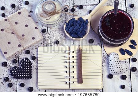 Open notebook with copy space, jars with jam and sugar, spoon with fresh berry, top view. Making fruit jam concept. Fresh berry on wooden table, summer still life and rustic food vintage background
