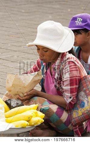 Ubud Bali Indonesia - July 30 2013. Balisese woman saling corn cobs to earn money to the people who goes to the temple.