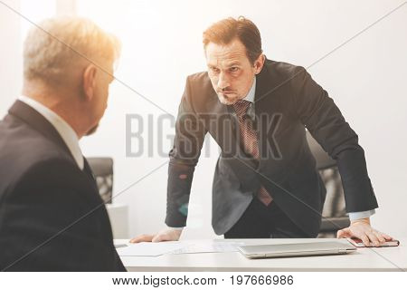 Completely different. Emotional impatient impulsive man calling for his worker for telling him he making a terrible mistake in his report and firing him