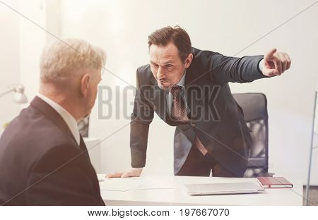 You dont belong here. Young ambitious emotional man being angry with his senior worker and asking him leaving his workplace as soon as possible