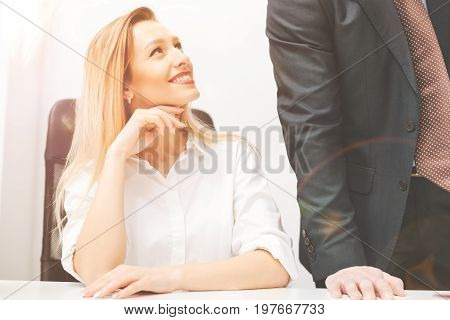 Lively discussion. Pretty friendly young lady sitting at her workplace and talking to her colleague as they enjoying a short break in the office