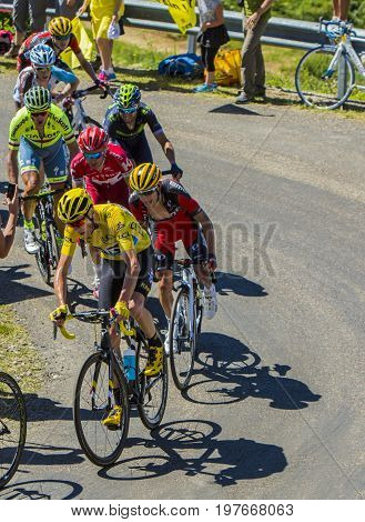 Col du Grand ColombierFrance - July 17 2016: Froome in Yellow Jersey riding in a group of cyclists on the road to Col du Grand Colombier in Jura Mountains during the stage 15 of Tour de France 2016.