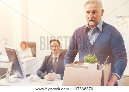 On the edge of retirement. Prepared sad serious man being fired and walking out of the bounding while taking his stuff with him in a box