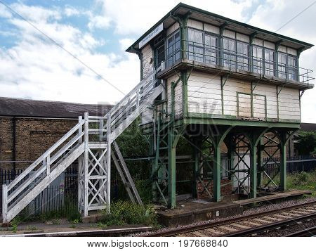 old british railway signal box with wooden white planks on an iron frame with white steps and track visible in the foreground taken in Canterbury kent