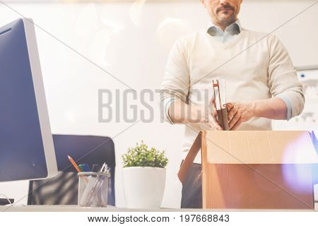 Ideas for own business. Intelligent sad ambitious man leaving the office and packing his belongings while being dismissed