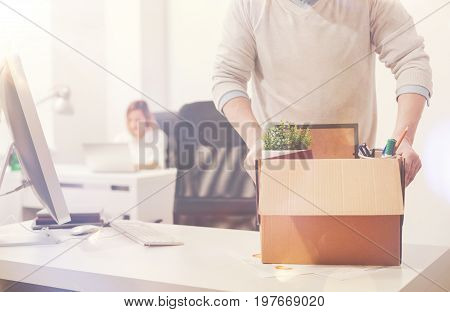 Only personal items. Young incompetent worker being dismissed and packing his belongings while leaving the office