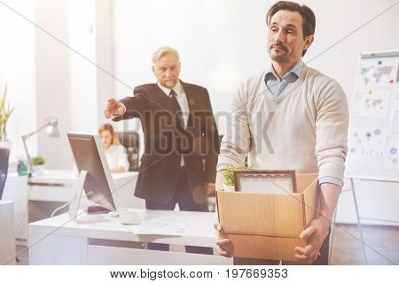 Door is that way. Distressed handsome young man holding all his stuff he packing in a box while leaving his workplace