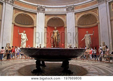 VATICAN, ROME, ITALY - JULY 15, 2017: Tourists and Hercules sculpture roman statues and round monolithic porphyry basin in Round Room of Pio-Clementino Museum in Vatican museums Vatican city Rome Italy