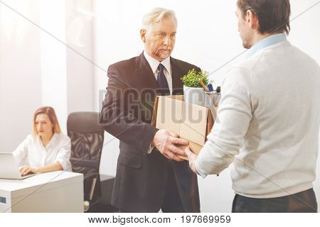 You are not welcome here. Solid persuasive mature man handing the worker his belongings as he dismissing him and asking leaving immediately