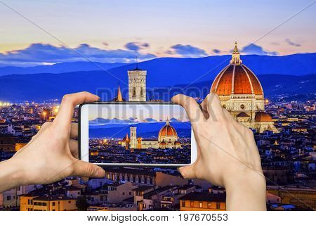 Tourist using smartphone taking a picture of Florence`s Cathedral at sunset, Florence, Italy