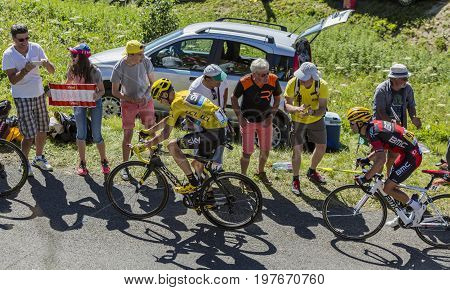 Col du Grand ColombierFrance - July 17 2016: Froome in Yellow Jersey and Richie Porte riding on the road to Col du Grand Colombier in Jura Mountains during the stage 15 of Tour de France 2016.