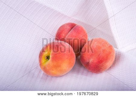 Close-up of a three whole and juicy peaches on the white background. Appetizing fruits of peaches or nectarines full of vitamins on a light fabric. Summer fruits. Vegetarian lifestyle.