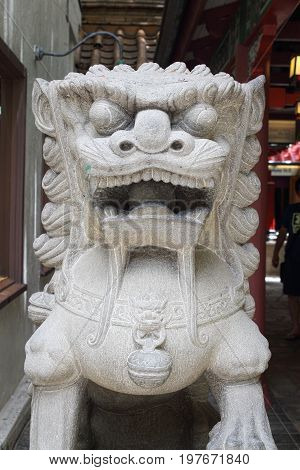 Honolulu Hawaii USA - May 25 2016: Downtown Waikiki Oriental lion figures are found throughout shopping areas full of holidaying tourists.