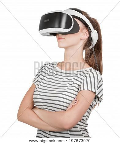 A slim girl is using a 3D virtual reality headset and crossed her arms, isolated on a white background. Professional audio equipment. A girl in virtual reality goggles. VR Glasses. Digital VR device.