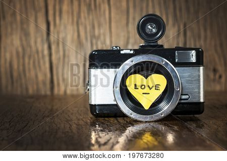 Retro camera with yellow heart love on wood background