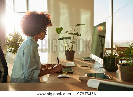Side view of female graphic designer working with digital drawing tablet and pen on a computer in office. African woman working at her desk.