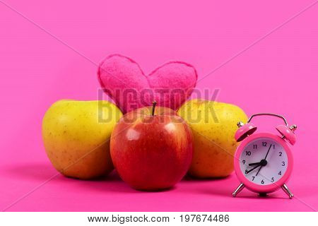 Love and diet. Apples of different colors with pink soft heart and rosy alarm clock in vintage style isolated on pink background. Healthy food for valentines day and regime concept