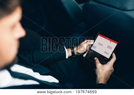 Businessman sitting in car planning and scheduling meetings on his organizer and using apps on smartphone. Business executive travelling by car and using phablet.