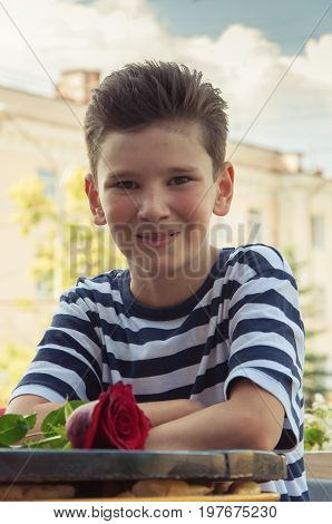 boy with rose at a table in an outdoor cafe. Concept: fashionable hairstyle, kids love