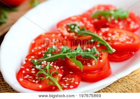 Fresh tomato slices, arugula rocket and sesame seeds salad. Low calorie salad on a white plate and burlap napkin. Diet lunch or dinner idea. Closeup