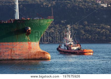 Red Tug Goes Near Bow Of Big Cargo Ship