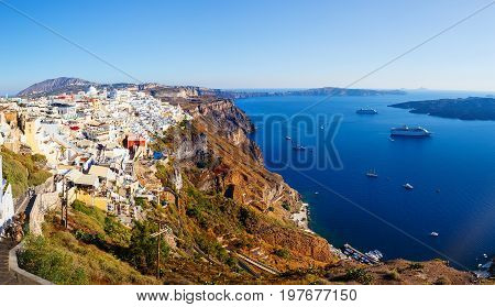 View of Fira village built on top of volcano cliff and blue sea Santorini island, Greece