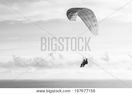Flying a tandem paraglider over the sea with views of the horizon.