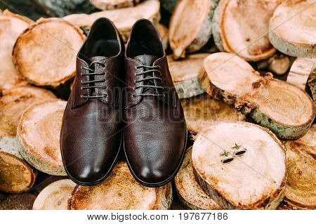Groom's shoes and cufflinks on a wooden background. Men's accessories. Close-up