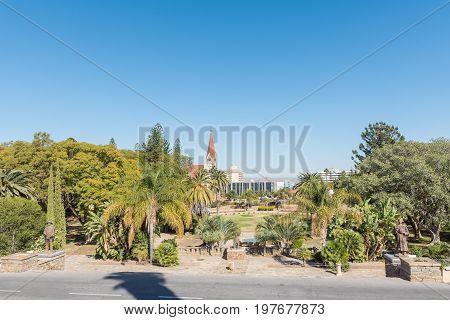 WINDHOEK NAMIBIA - JUNE 17 2017: Gardens at the Tintenpalast the Namibian parliament building in Windhoek. Statues of Hendrik Samuel Witbooi Hosea Kutako and Theofelos Hamutumbangela visible