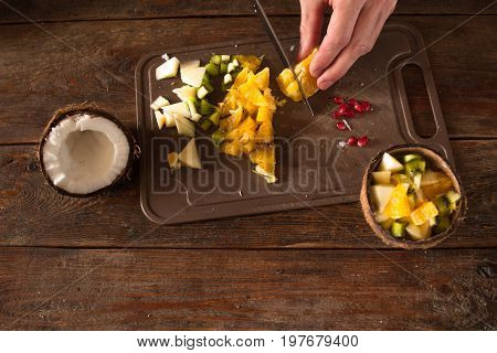 Preparing of tropical fruit salad in coconut shell. Orange, apple, kiwifruit and pomegranate ingredients are cut on brown wooden desk