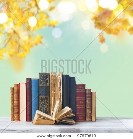 set of old books with open one on white wooden desktop, fall leaves background