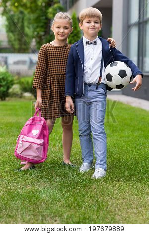 Adorable Schoolkids Holding Backpack And Soccer Ball While Standing Together Near School