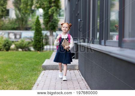 Cute Little Redhead Schoolgirl Holding Book And Walking Near School