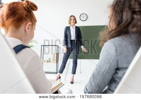 smiling young teacher holding chalk and looking at schoolkids during lesson
