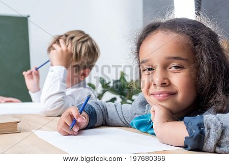 Cute Multiethnic Schoolkids Drawing While Sitting At Desk In Class