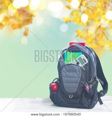 School backpack full of supplies on white desktop, fall leaves background