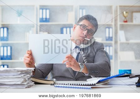 Businessman smoking at work in office holding a blank message
