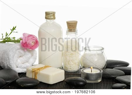 Spa setting with candle, ranunculus .towel ,towel ,salt in bottle, on mat