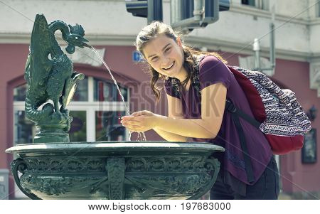 Young girl travel and drinking  water from the fountain