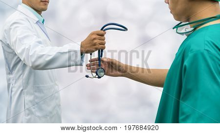 Doctor Giving Stethoscope To Surgeon (referral)