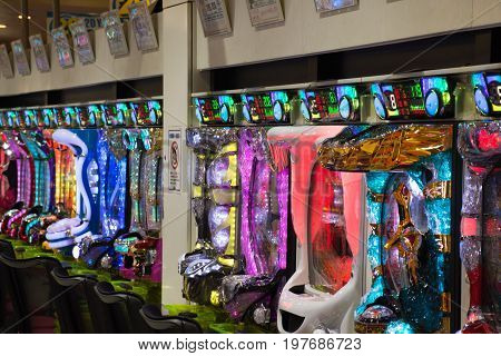 Row of pachinko machines in a parlor with colorful neon lights.