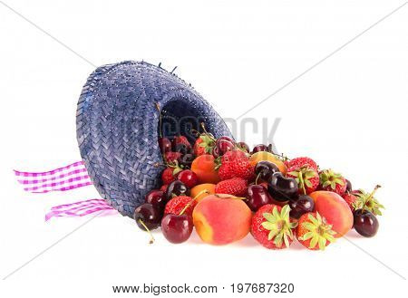 Assortment fresh fruit in blue summer hat isolated over white background