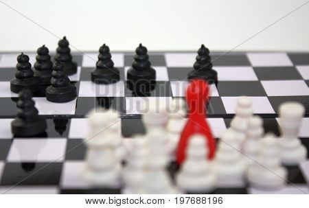 Chess game with selective focus to black pawn pieces with blurry white group with red ludo figure leader. Company competition or conflict of nationalities.