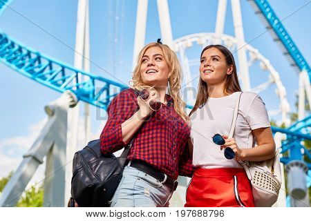 Portrait of two beautiful young women enjoying sunny day in amusement park standing against rides and Ferris wheel