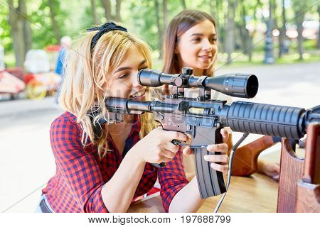 Portrait of beautiful blond woman aiming with big rifle at outdoor game tent in amusement park