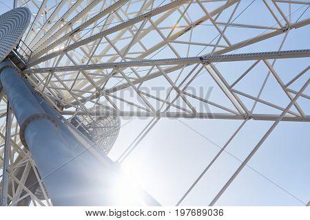 Low angle closeup of huge modern Ferris wheel against blue sky in amusement park