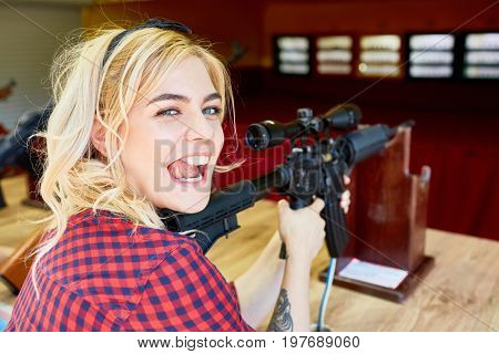 Portrait of cheeky blond girl holding big rifle at shooting stand in amusement park