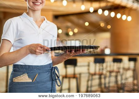 Young waitress carrying tray with cup of hot drink for client