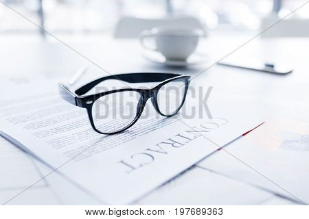 Composition With Eyeglasses And Business Contract On White Desk